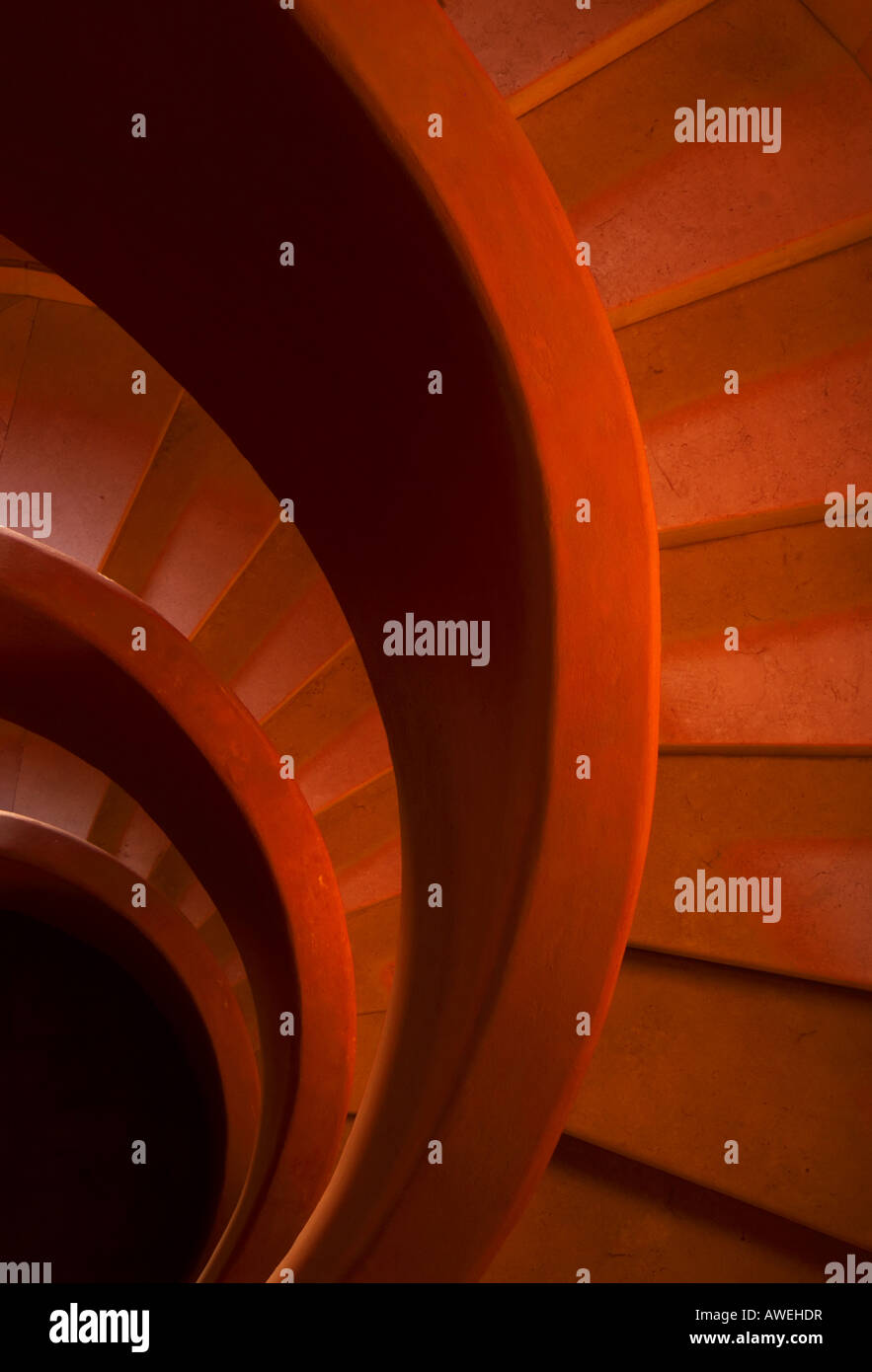 Red stone spiral stairs A close up of one side - Stock Image
