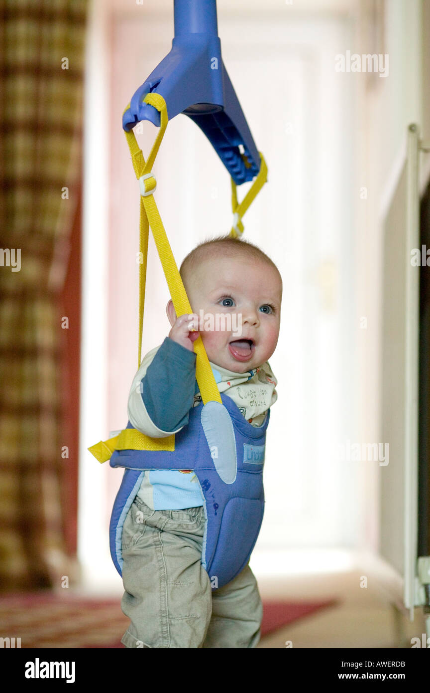 A Six Month Old Baby Boy In A Bouncer Suspended From A Door Frame