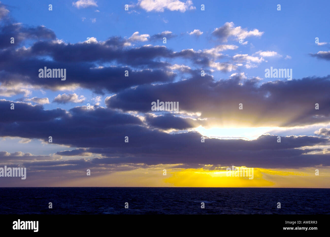 Sunset with sunburst and clouds over the Atlantic Ocean from a cruise ship. - Stock Image