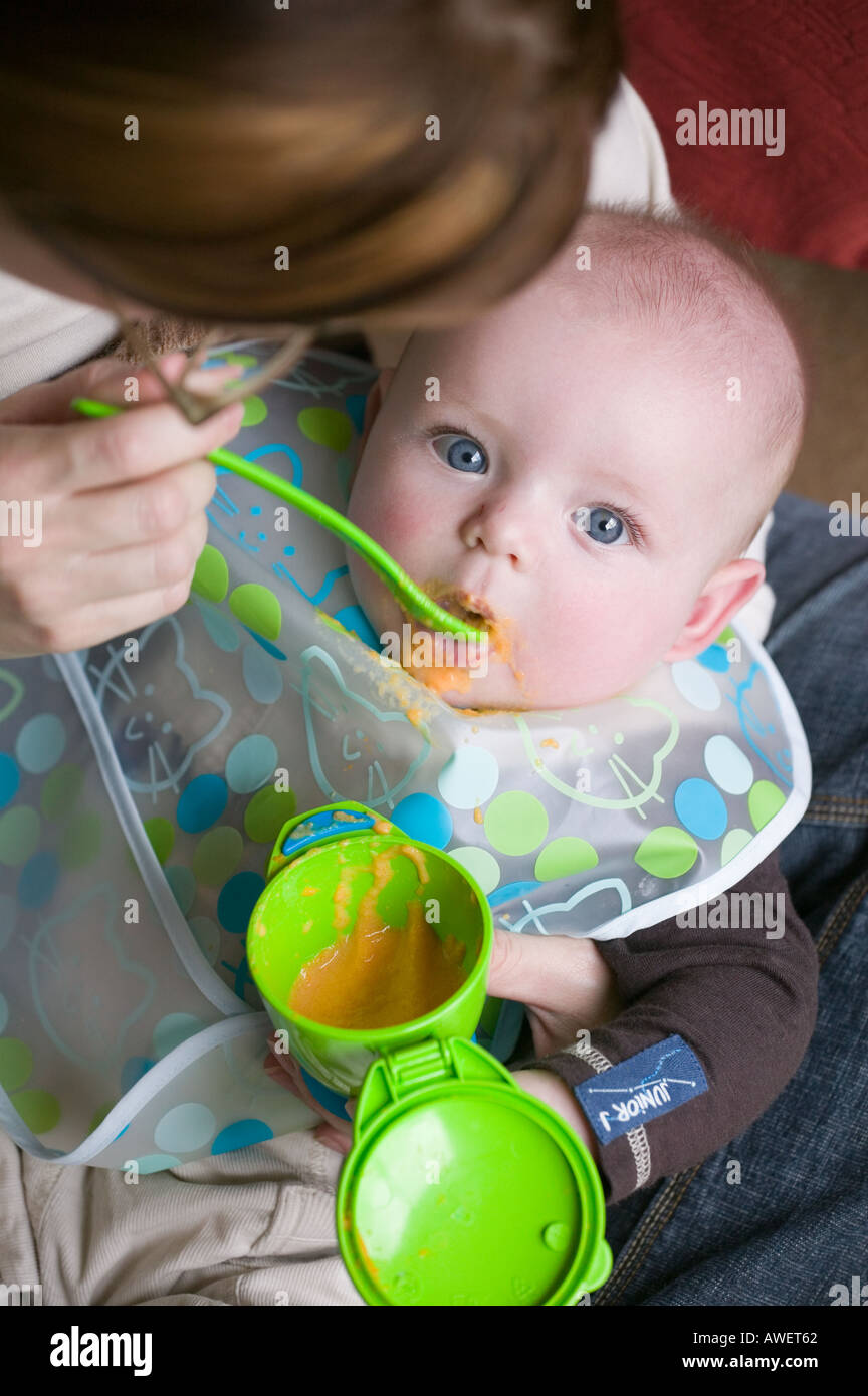 A ffive month old baby boy tries solid food for the first time - Stock Image