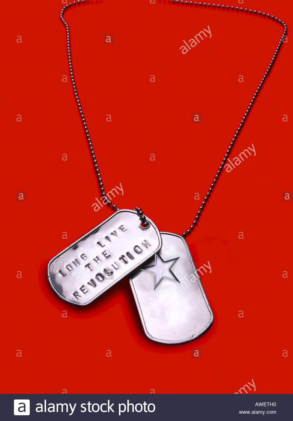 Close up of two military identification dog tags on a chain. Red background - Stock Image