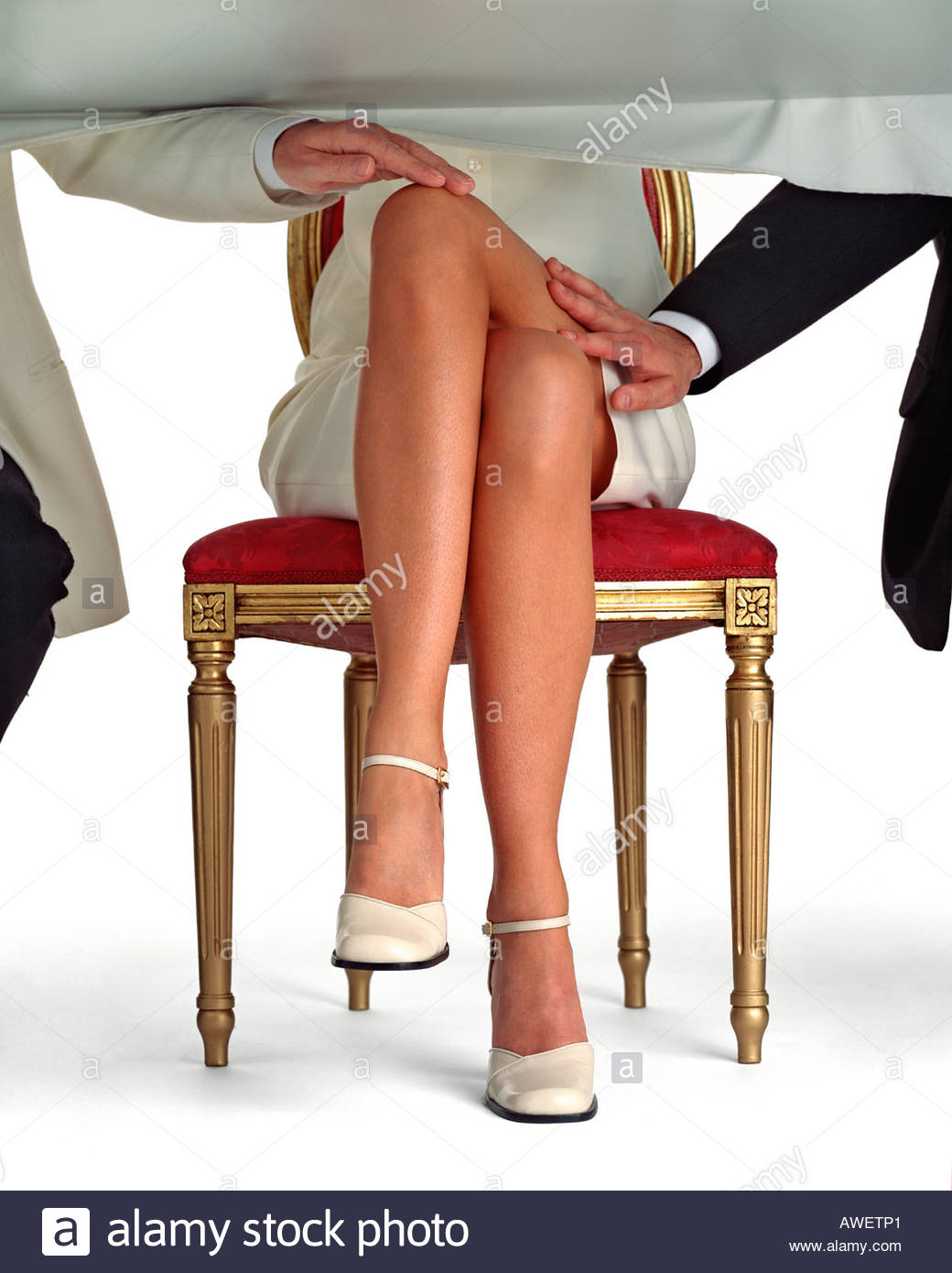 Womans legs crossed under a table while the men each side touch