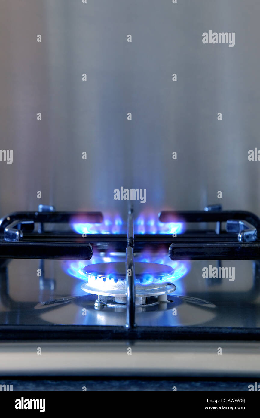Two gas rings alight on a modern brushed steel hob - Stock Image