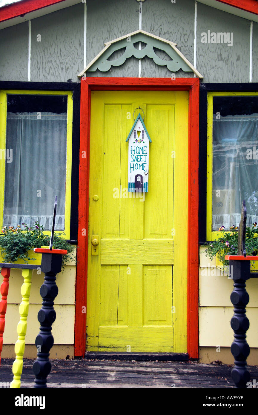 A bright yellow door and Home Sweet Home sign in Waldheim Saskatchewan Canada - Stock Image