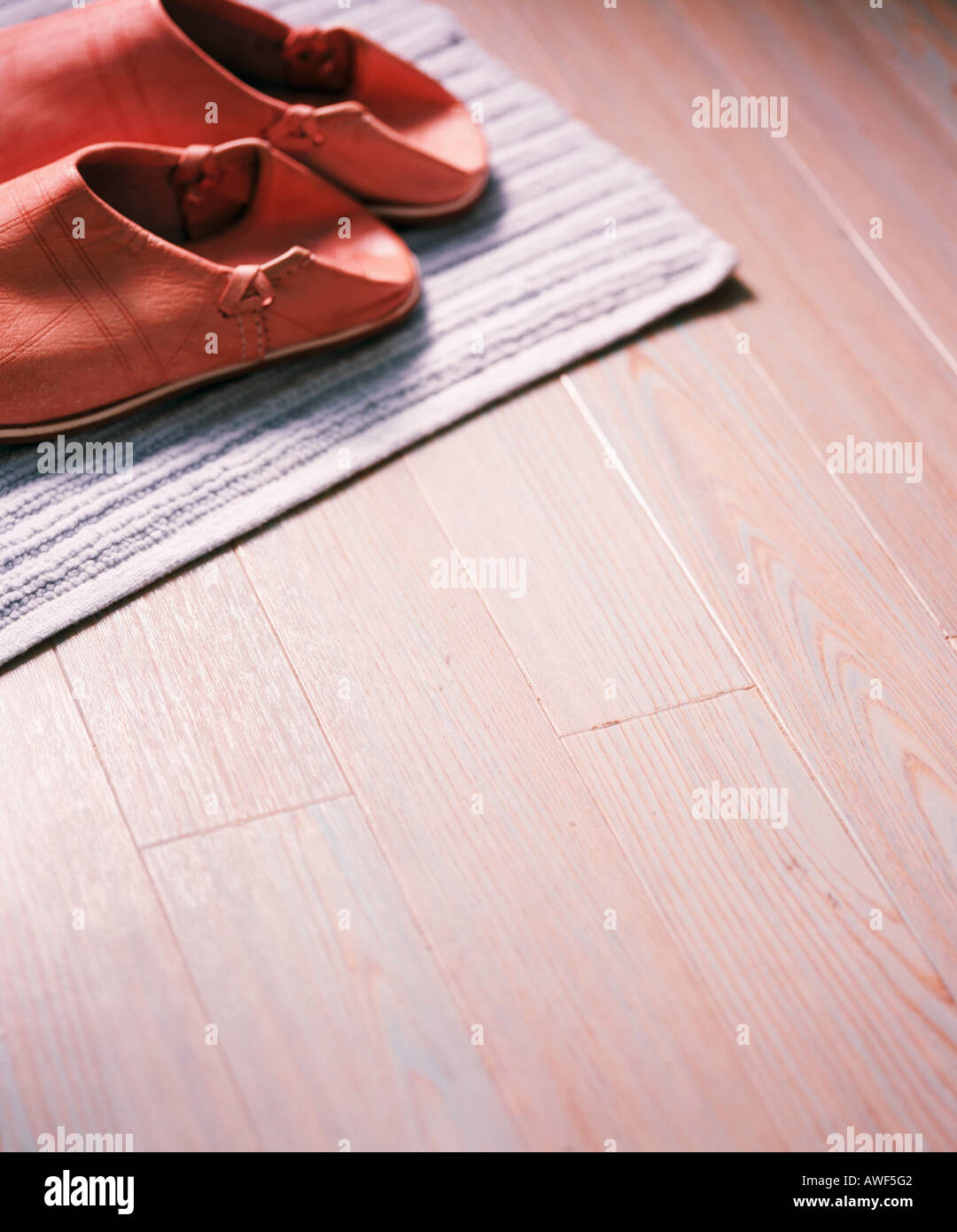 4f2703e54 Close-up of red leather Moroccan slippers on mat on wooden floor - Stock  Image