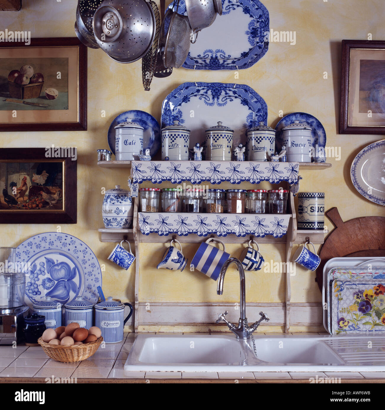 Close-up of blue+white plates and cups on small shelves with decorative fabric edging above double white kitchen sinks & Close-up of blue+white plates and cups on small shelves with Stock ...