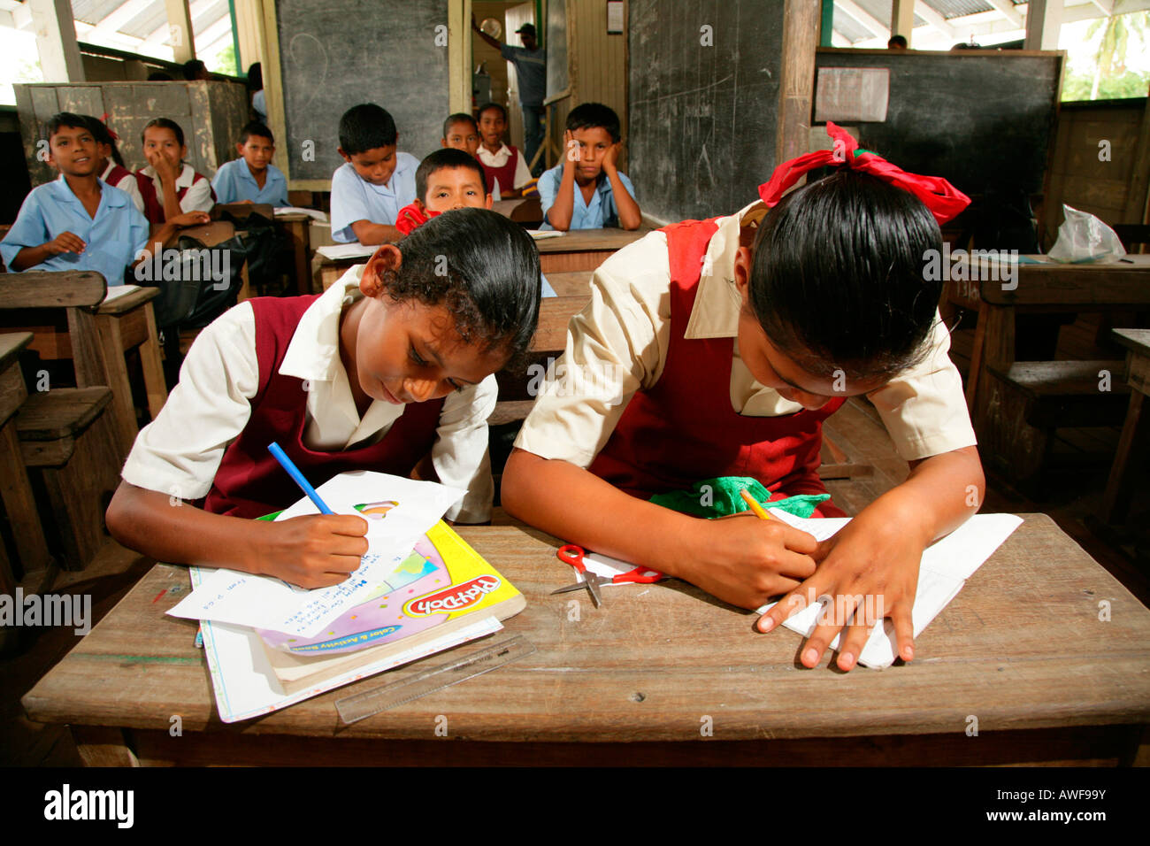 Schoolgirls in uniform during class, Amerindians, tribe of the Arawak, Kamuni river in the Guayana rainforest, South Stock Photo