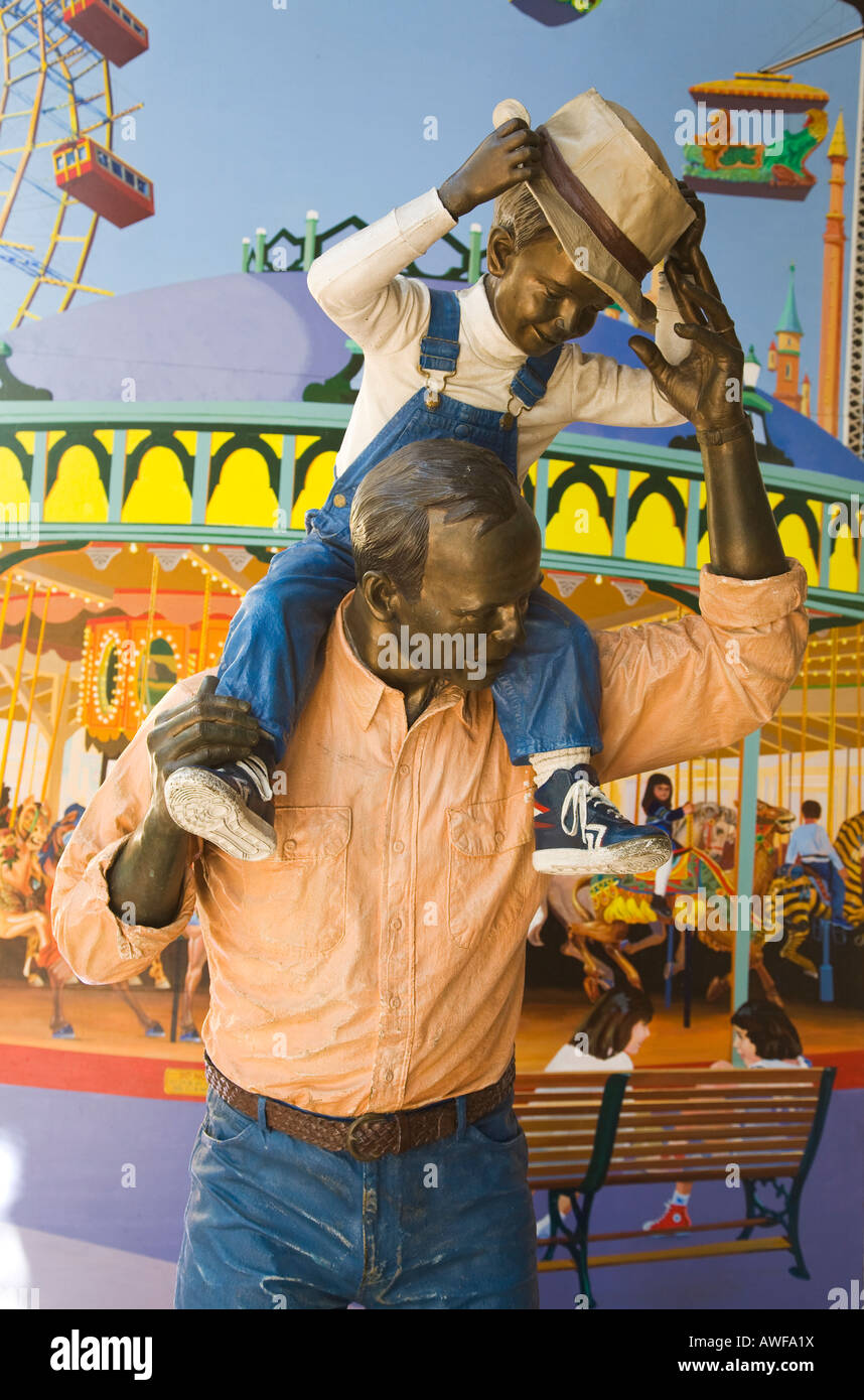 CALIFORNIA Santa Barbara Statue of man holding boy on shoulders lifelike life size realistic colorful carousel mural - Stock Image