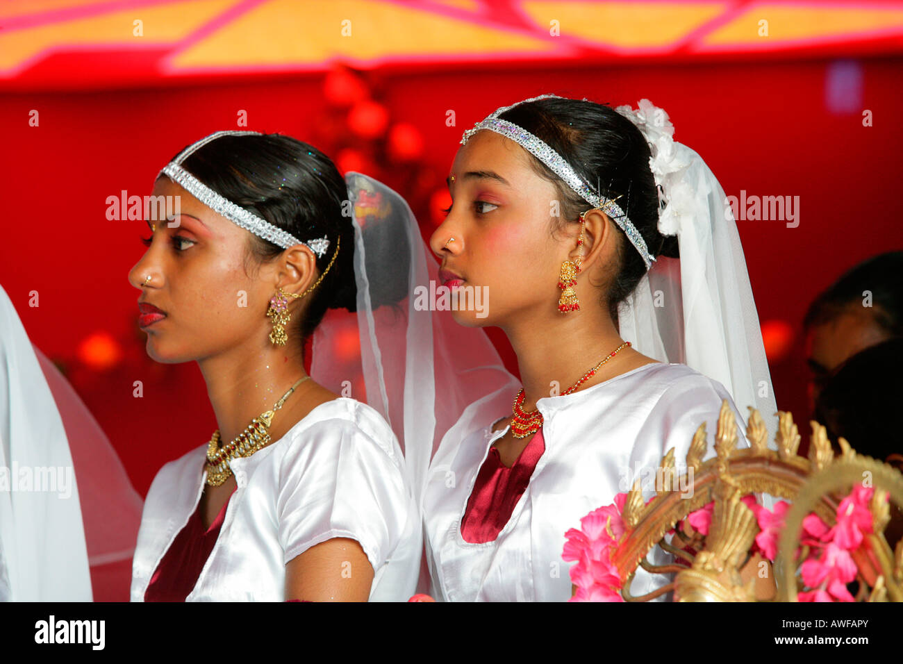 Girls of Indian ethnicity with Shiva figure at a Hindu Festival in Georgetown, Guyana, South America - Stock Image