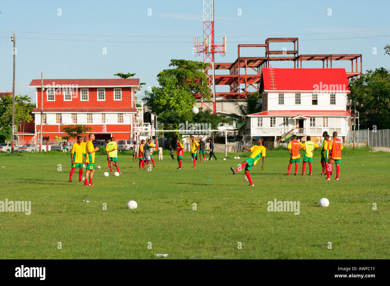 Young people playing football on a lawn in Georgetown, Guyana, South America - Stock Image