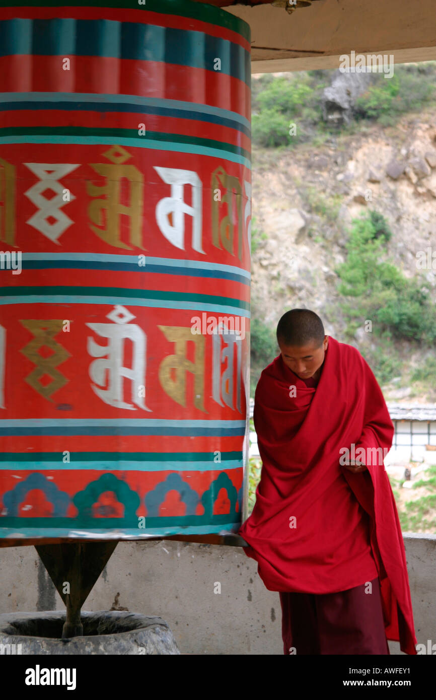 Tibetan monk praying with a spinning prayer wheels, Bhutan Stock Photo