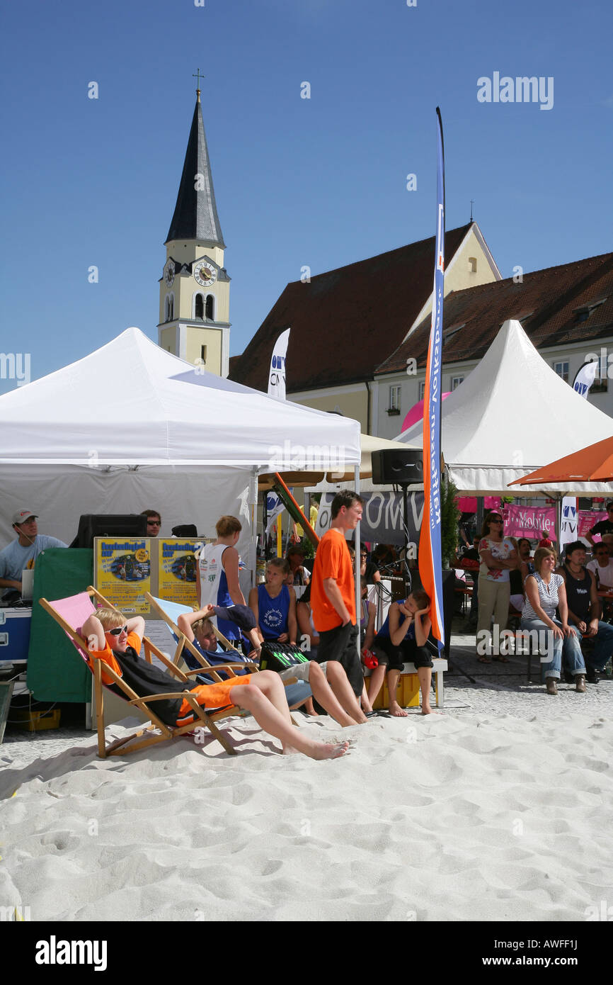 Kids sitting on deck chairs, spectators at a beach volleyball tournament on the main square of Muehldorf am Inn, Stock Photo