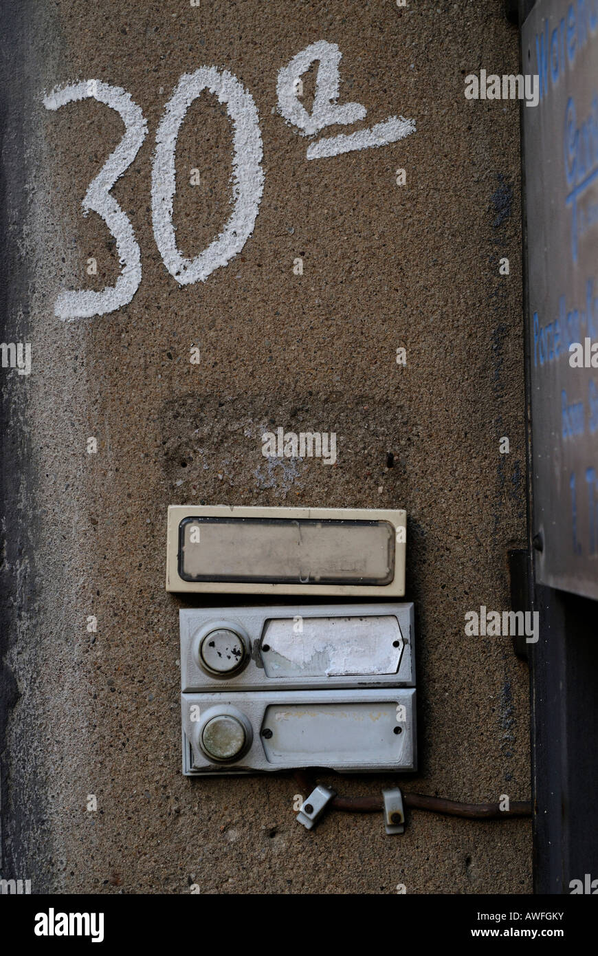 Apartment building entrance, closeup showing old doorbell listing tenants' names - Stock Image