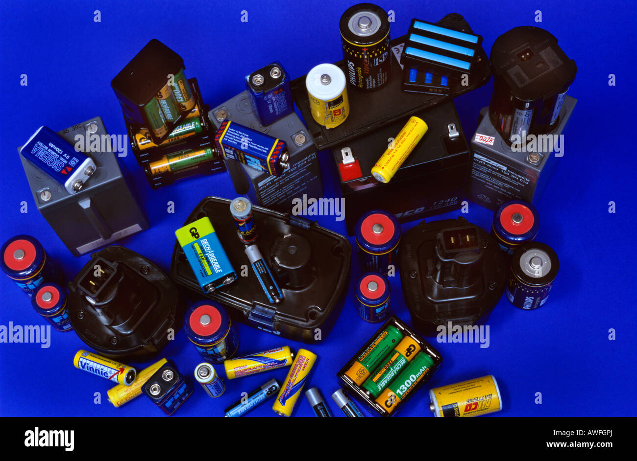 Old rechargeable batteries against a blue backdrop - Stock Image