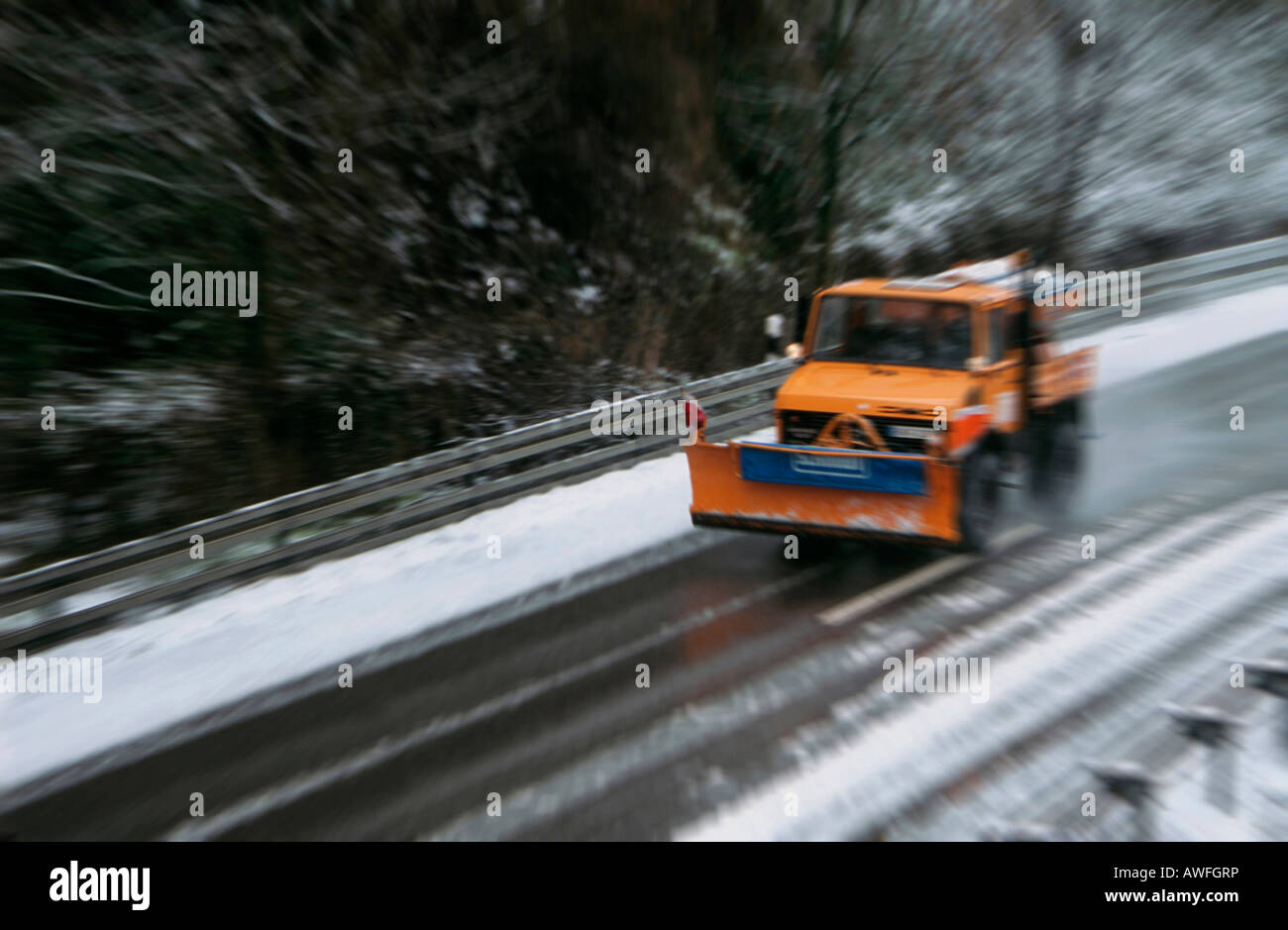 Winter road maintenance vehicle driving on a highway, Bergisches Land, Germany, Europe - Stock Image