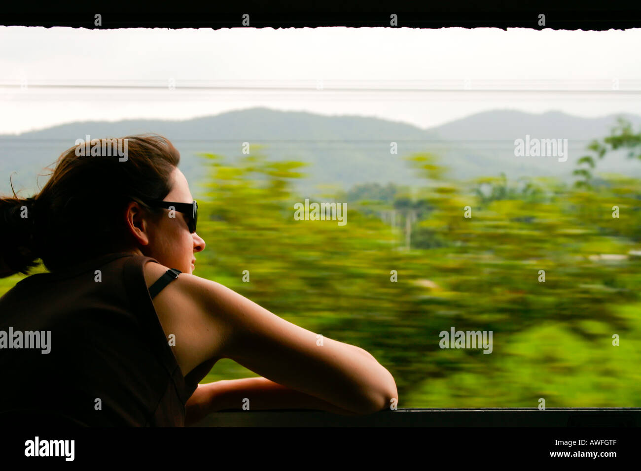 Woman traveling travelling alone on a train, backpacking, En route by train to Chiang Mai, Northern Thailand south east asia - Stock Image