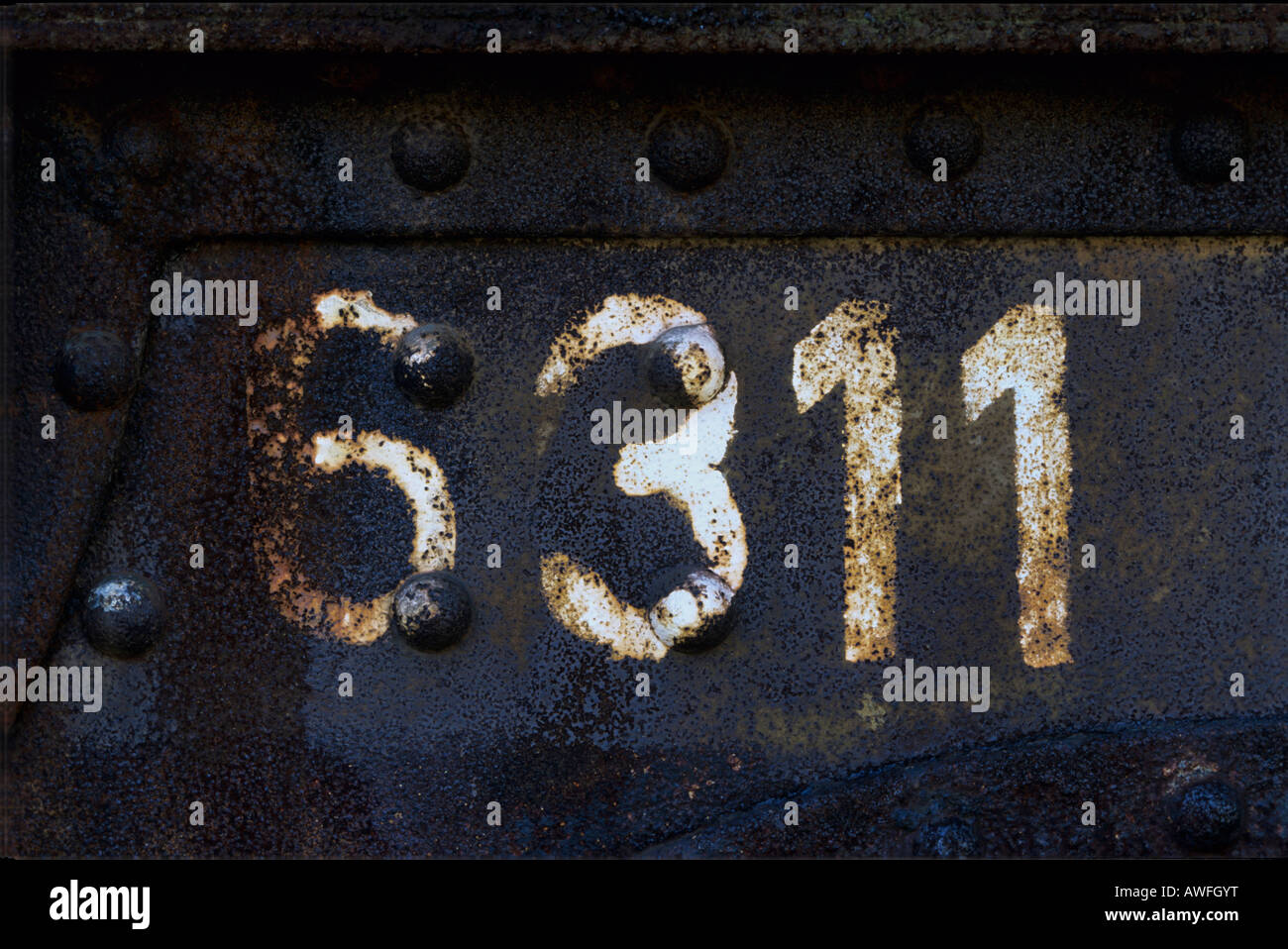 White numbers painted on a rusty old metal surface - Stock Image