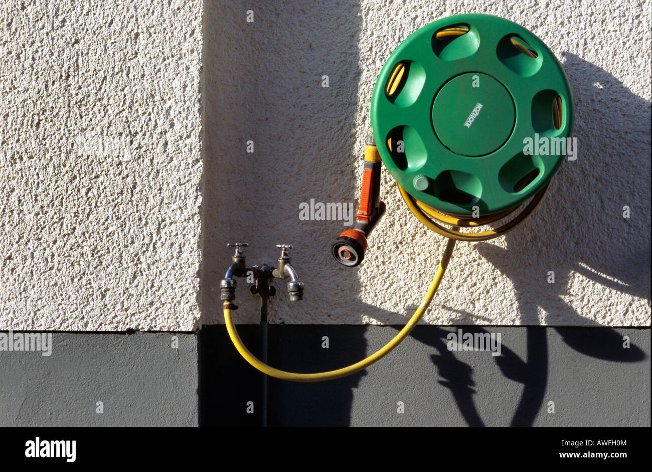 Water tap, rolled garden hose Stock Photo