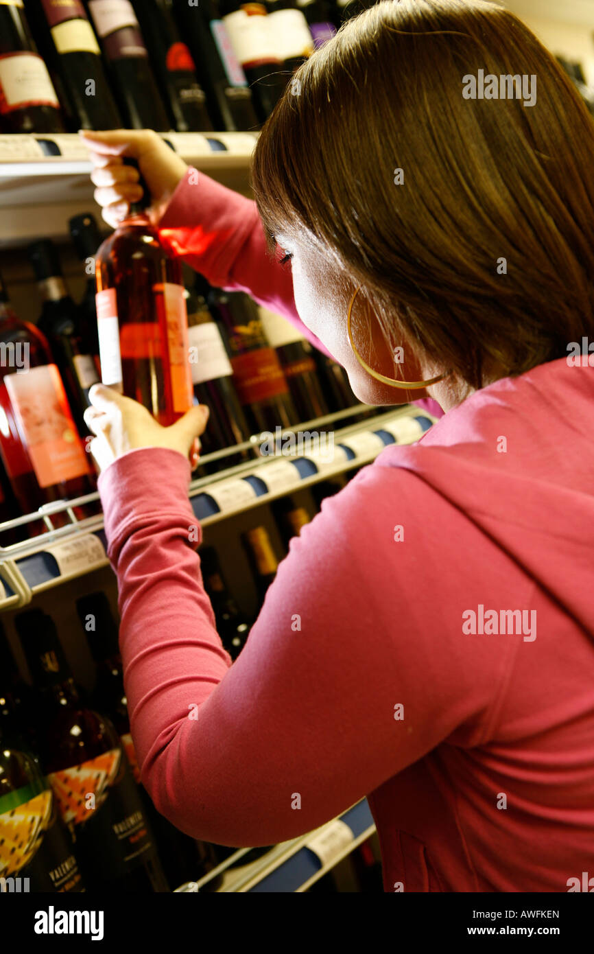 Teenager buying alcohol from off license store Underage drinking - Stock Image