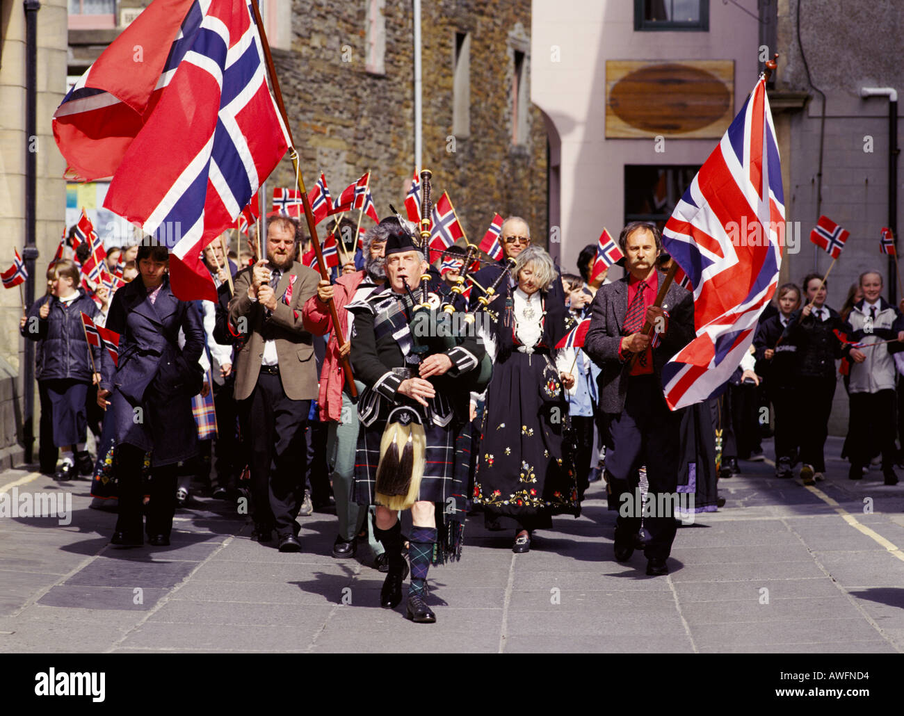 dh Norwegian Constitution Day KIRKWALL ORKNEY Bagpiper leading street parade Albert street Flags procession Stock Photo