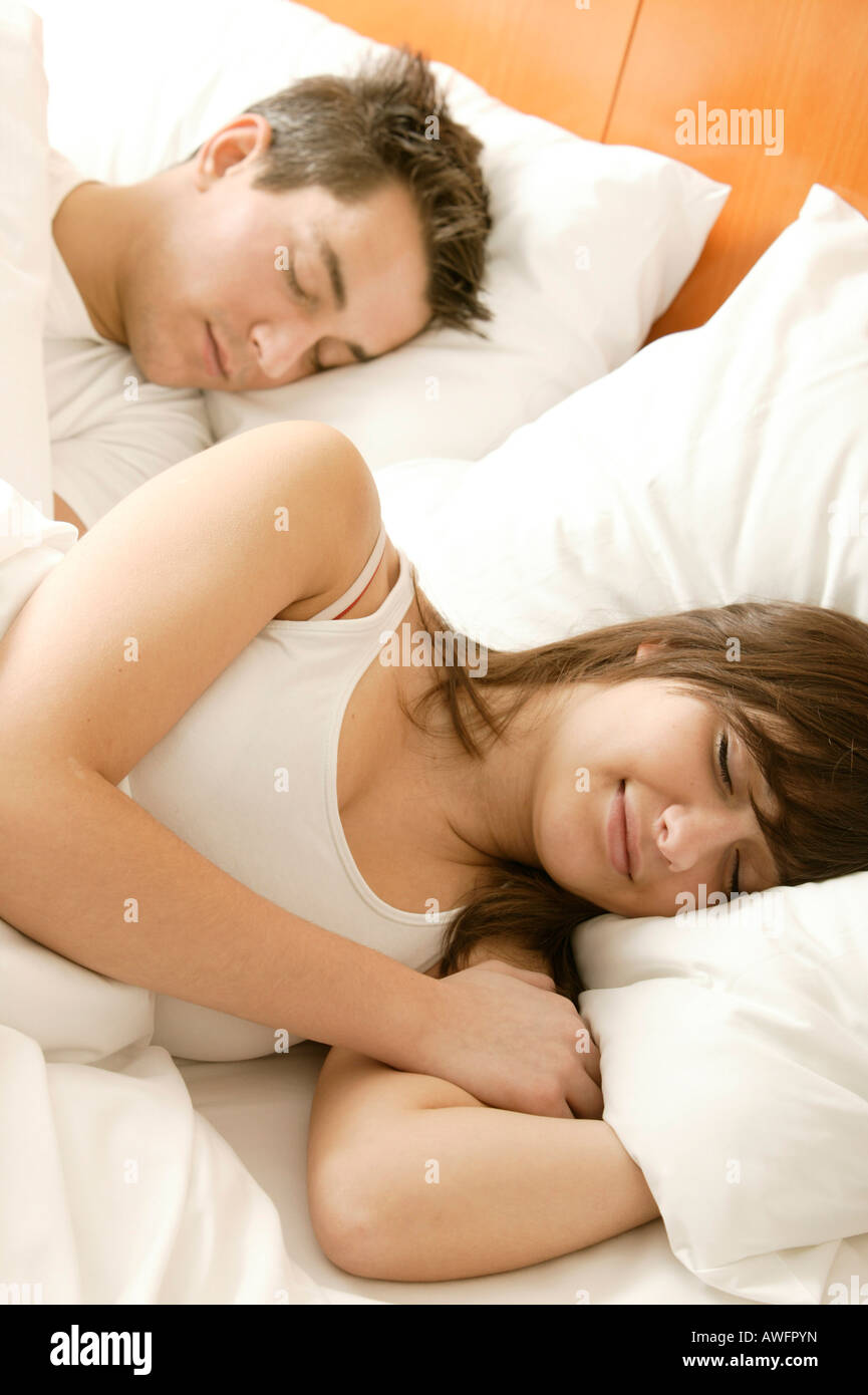 Young couple sleeping in bed, smiling - Stock Image