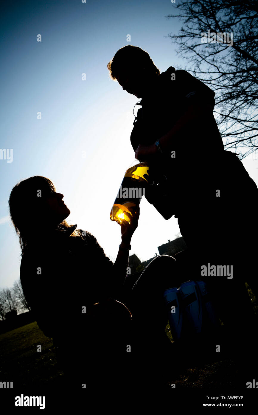 Teenager drinking bottle of alcohol in a park Police officer confiscating Underage drinking - Stock Image