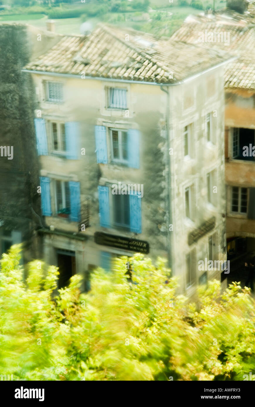 typical provencal building seen through a patterned window in Gordes, Provence, France - Stock Image