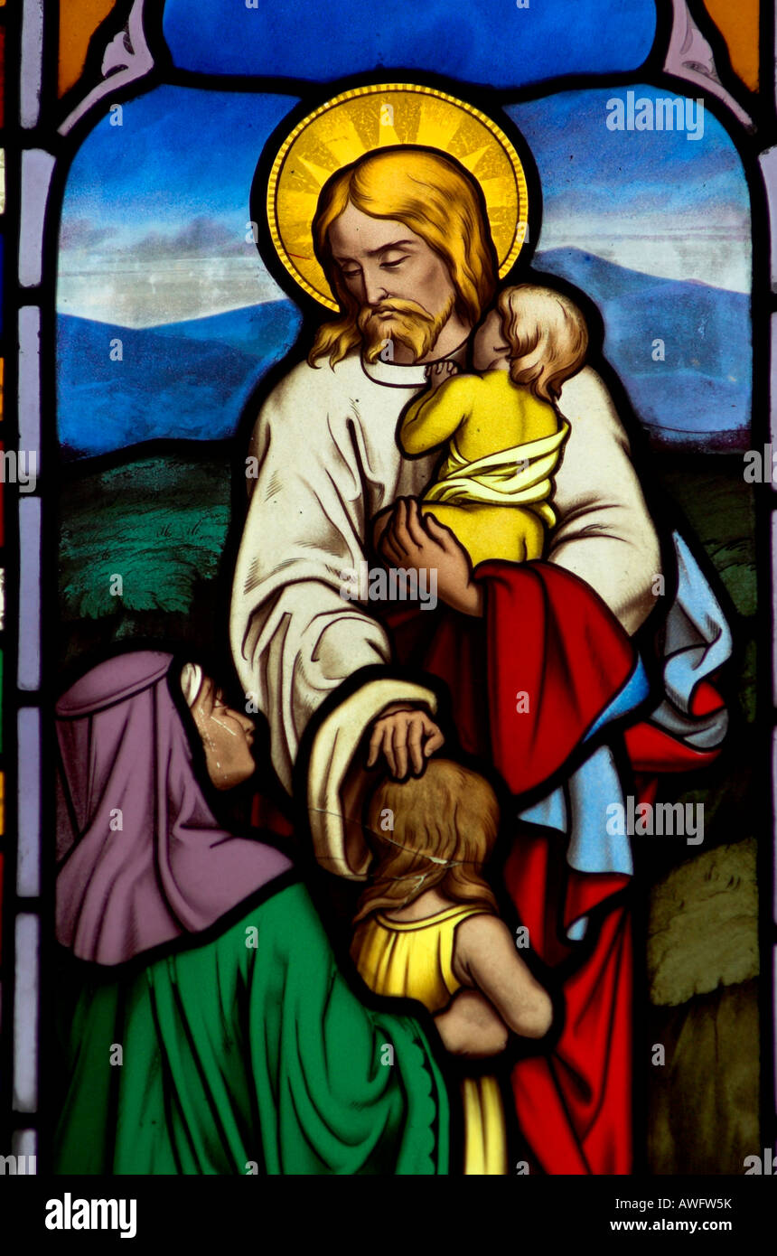 A stained glass window in Gloucester cathedral of Jesus comforting an infant and a child - Stock Image