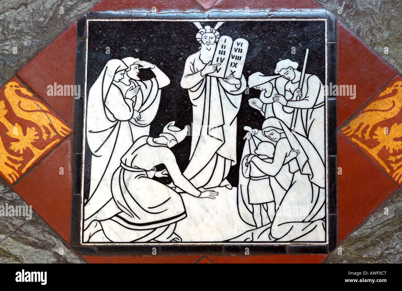 A floor tile in Gloucester Cathedral depicting Moses with the Ten Commandments - Stock Image