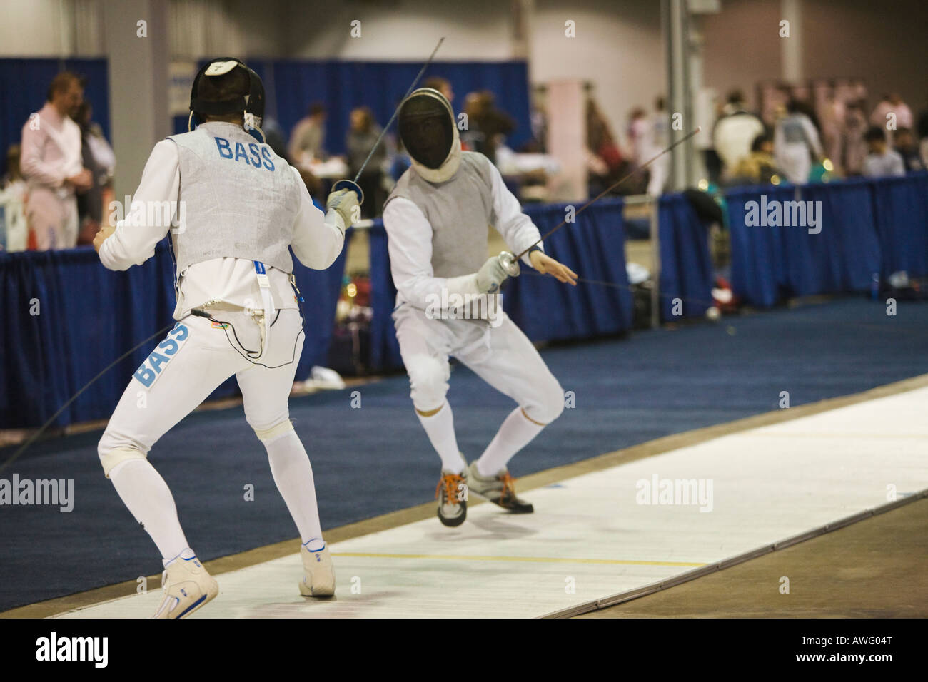 SPORTS Fencing competition bout male foil competitors on strip during match lunging toward opponent - Stock Image