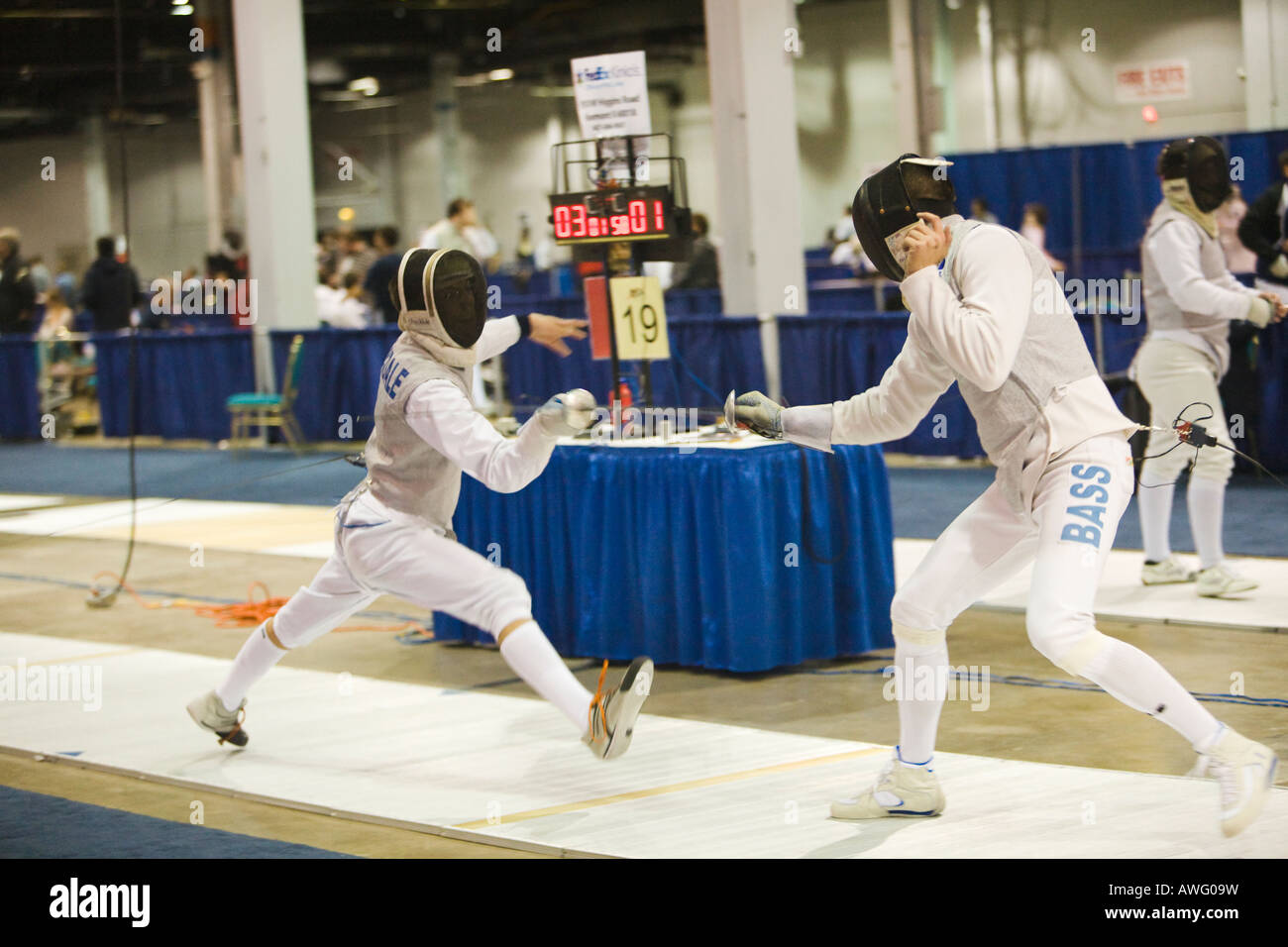 SPORTS Fencing competition bout male foil competitors on strip during match lunging toward opponent scoreboard - Stock Image