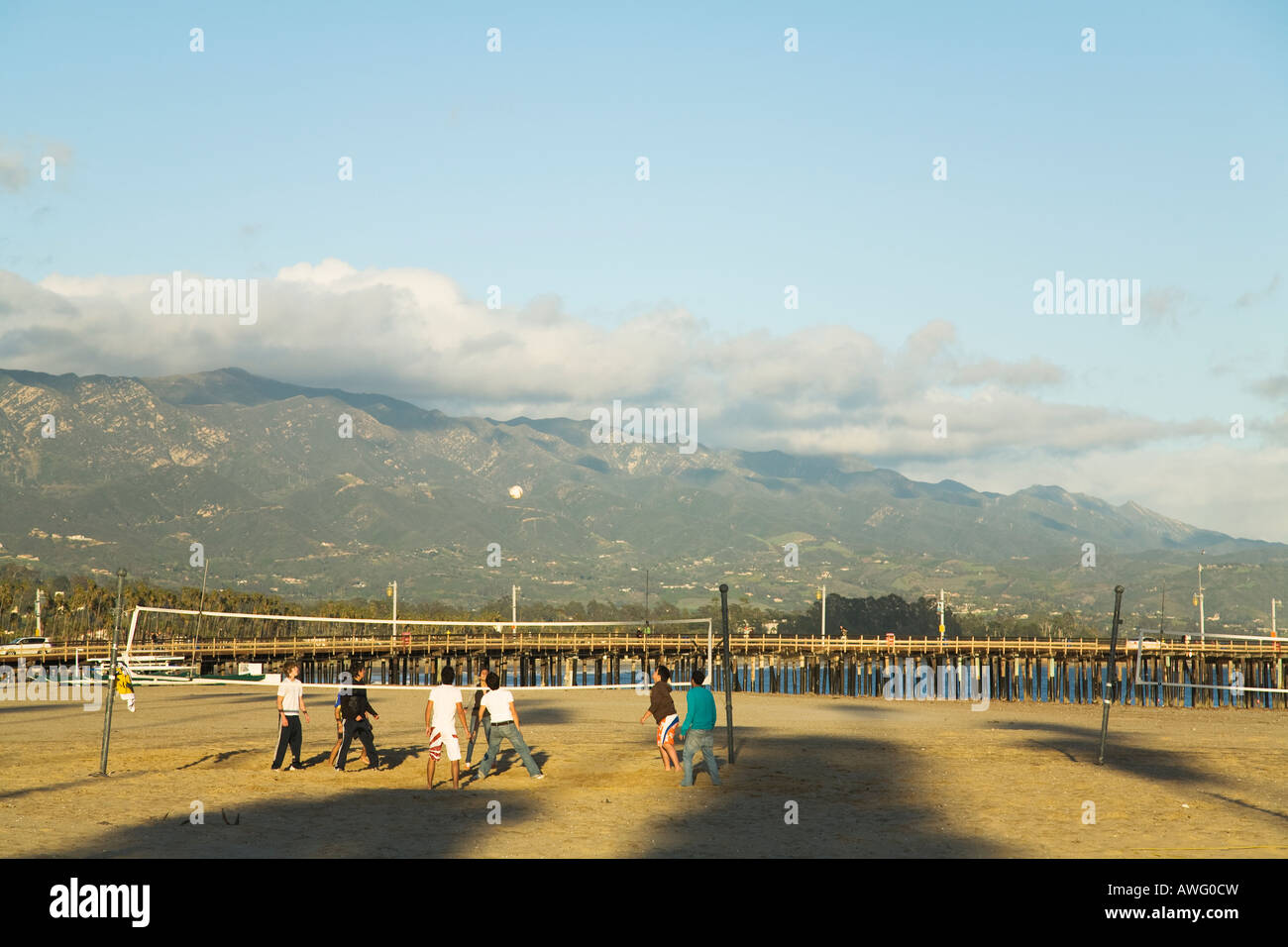CALIFORNIA Santa Barbara High school students playing beach volleyball on West Beach Stearns Wharf and mountains Stock Photo
