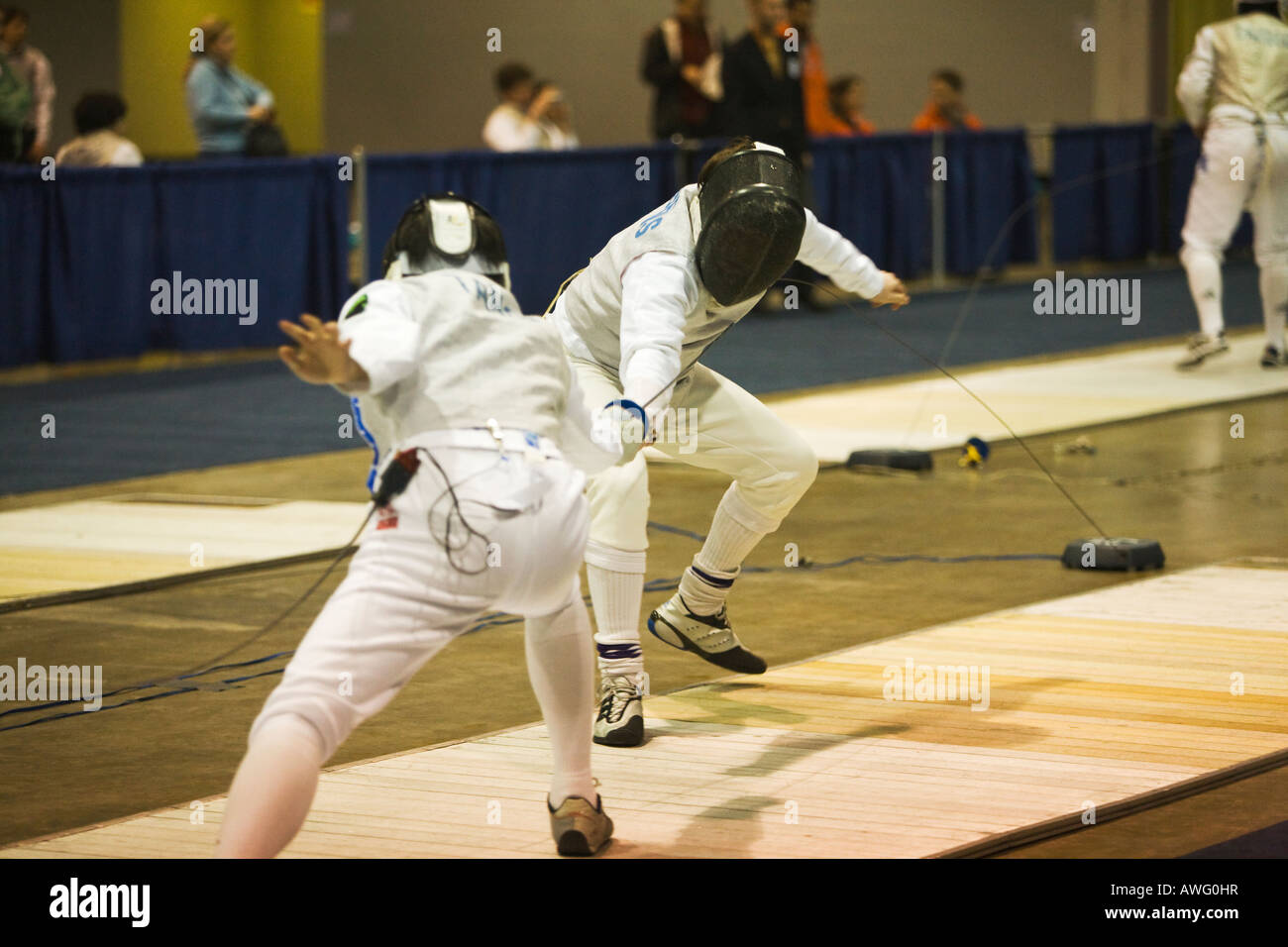 SPORTS Fencing competition bout male foil competitors on strip during match touch on lame jacket - Stock Image