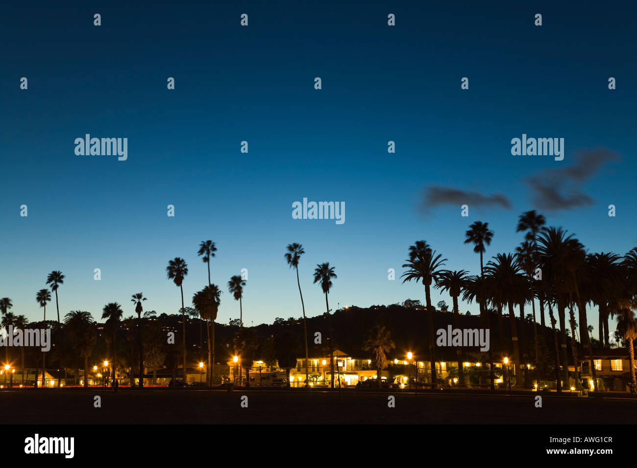 CALIFORNIA Santa Barbara Lights in hotel buildings on Cabrillo Boulevard at dusk palm trees and mountain - Stock Image