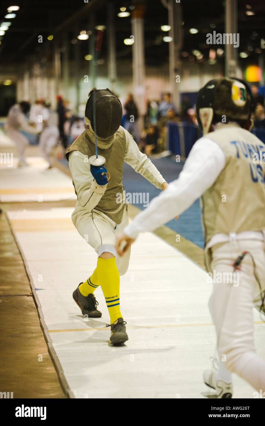 SPORTS Fencing competition bout male foil competitors on strip during match opponent with weapon raised - Stock Image