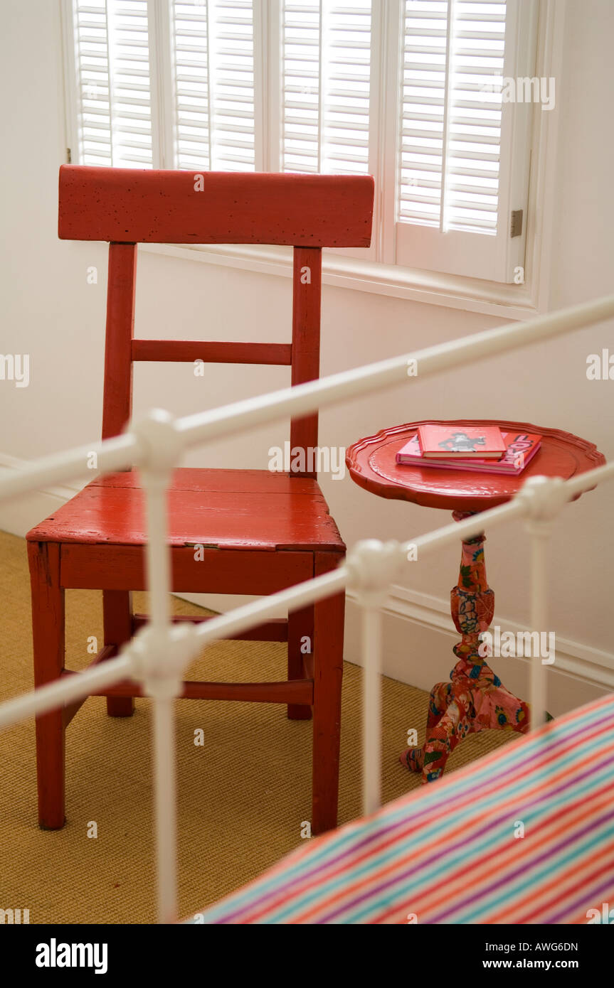 Red wooden chair and circular table at foot of wrought iron bed Stock Photo