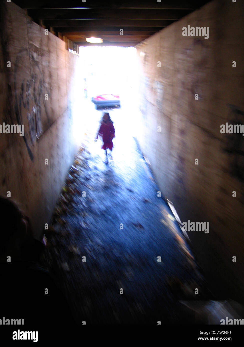Young girl emerging from dark enclosed walkway - Stock Image