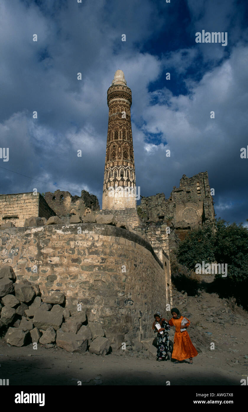 Children passing the minaret by the ruined Palace of Queen Arla, in the town of Jibla, near Ibb, Yemen. - Stock Image