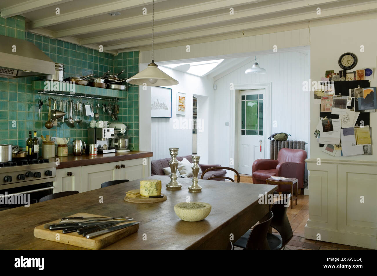 Open plan kitchen with turquoise tiles and beamed ceiling - Stock Image