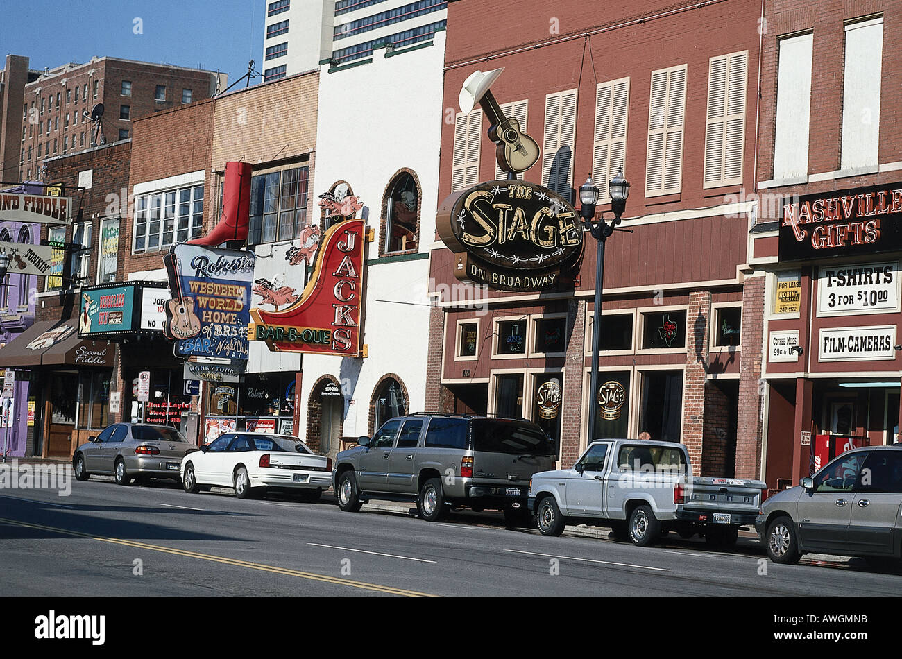 USA, Tennessee, Nashville, unlit neon signs above venues and stores lining downtown street with parked vehicles below - Stock Image