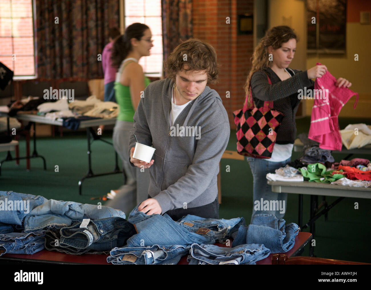 A young man inspects a pair of denim jeans at a clothing swap at the University of Puget Sound in Tacoma, WA, USA. - Stock Image