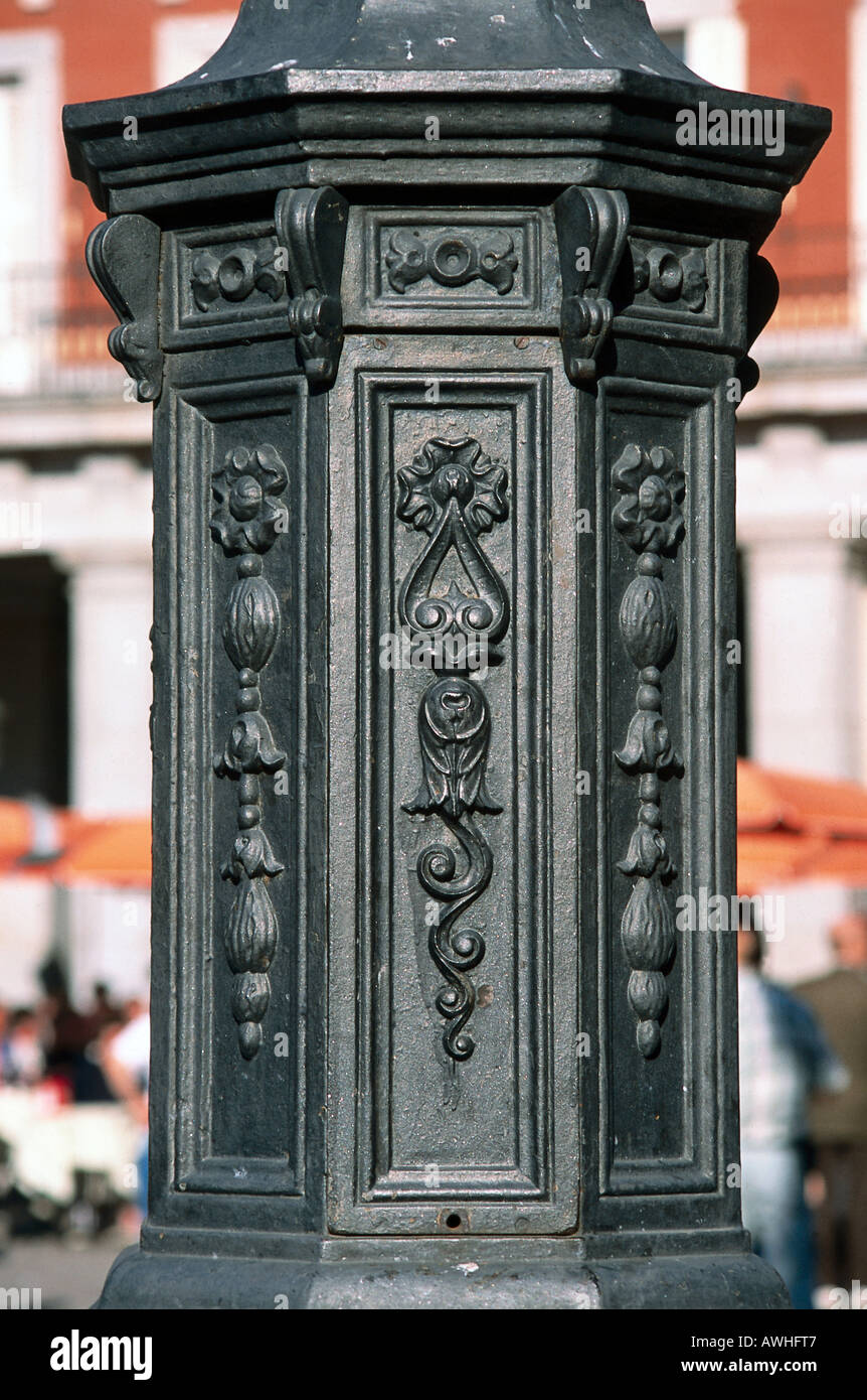 Spain, Madrid, Plaza Mayor, decorative patterns engraved on modern lamppost near statue of Felipe III, low section, close-up - Stock Image