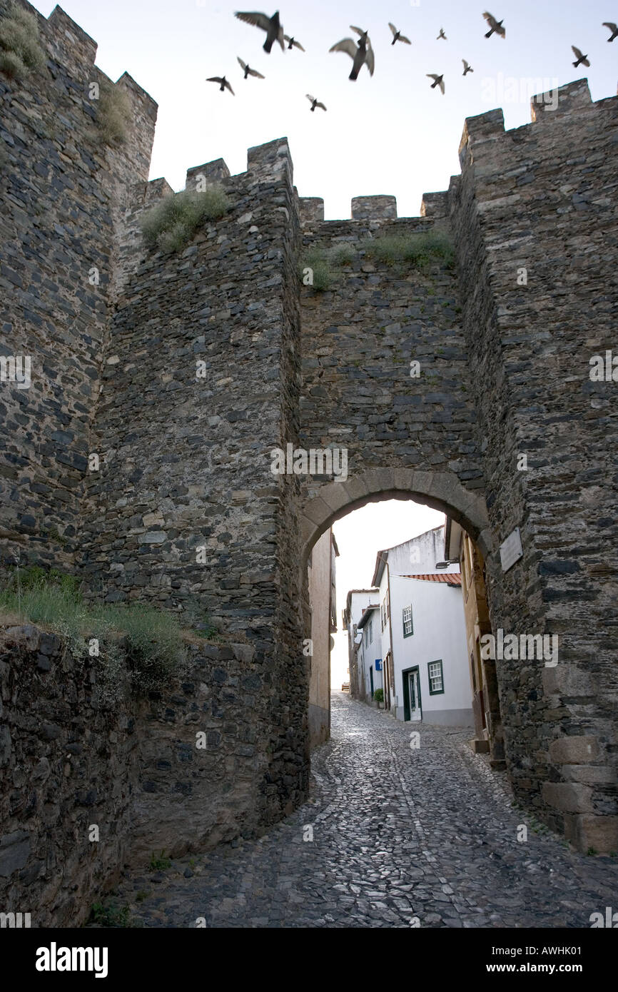 Pidgeons fly over the one of two roads leading through the walls of the 13th century citadel above the town of Bragaca, Portugal - Stock Image