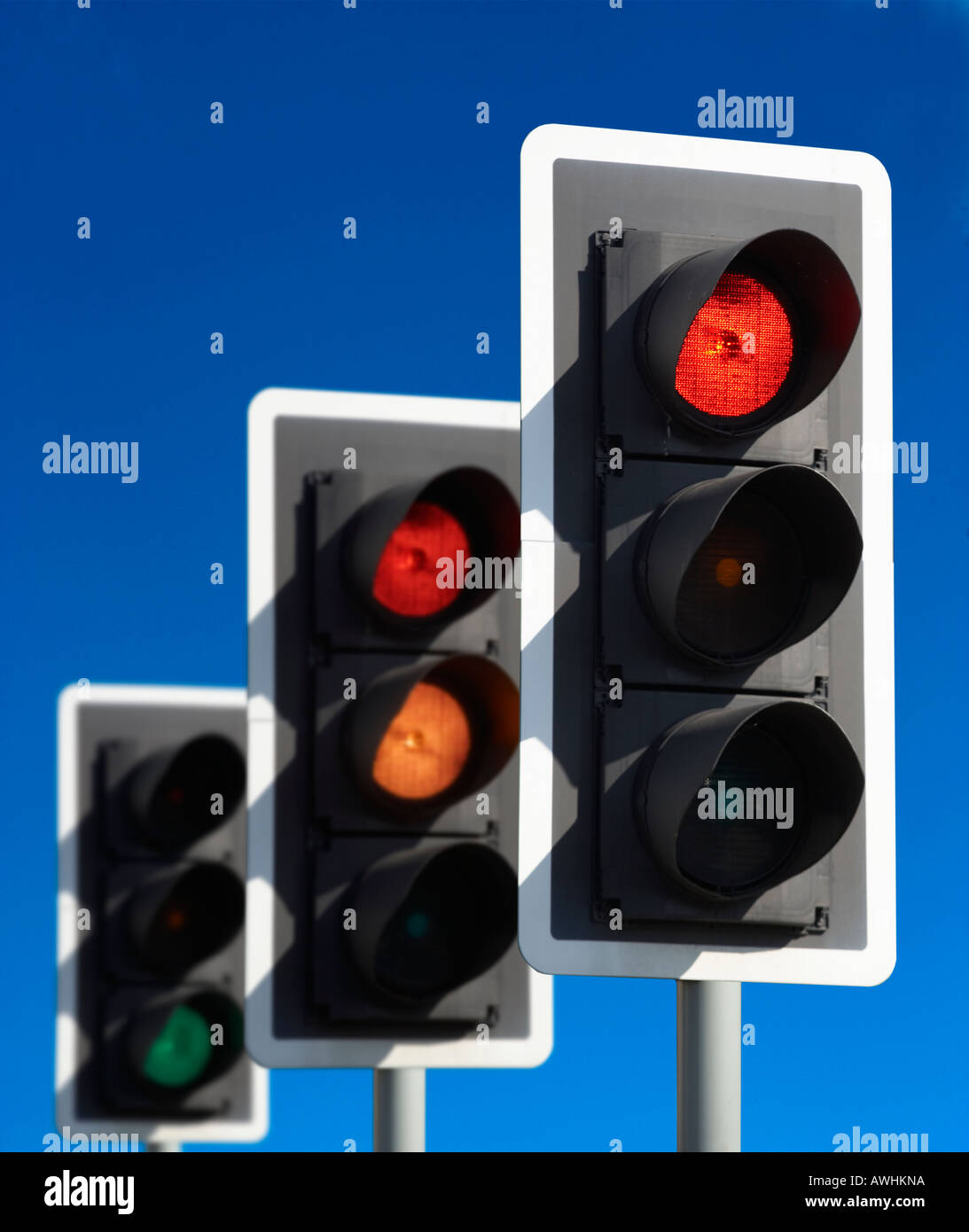 ROW OF THREE ROAD TRAFFIC LIGHTS SHOWING RED AMBER GREEN SEQUENCE WITH BLUE SKY - Stock Image
