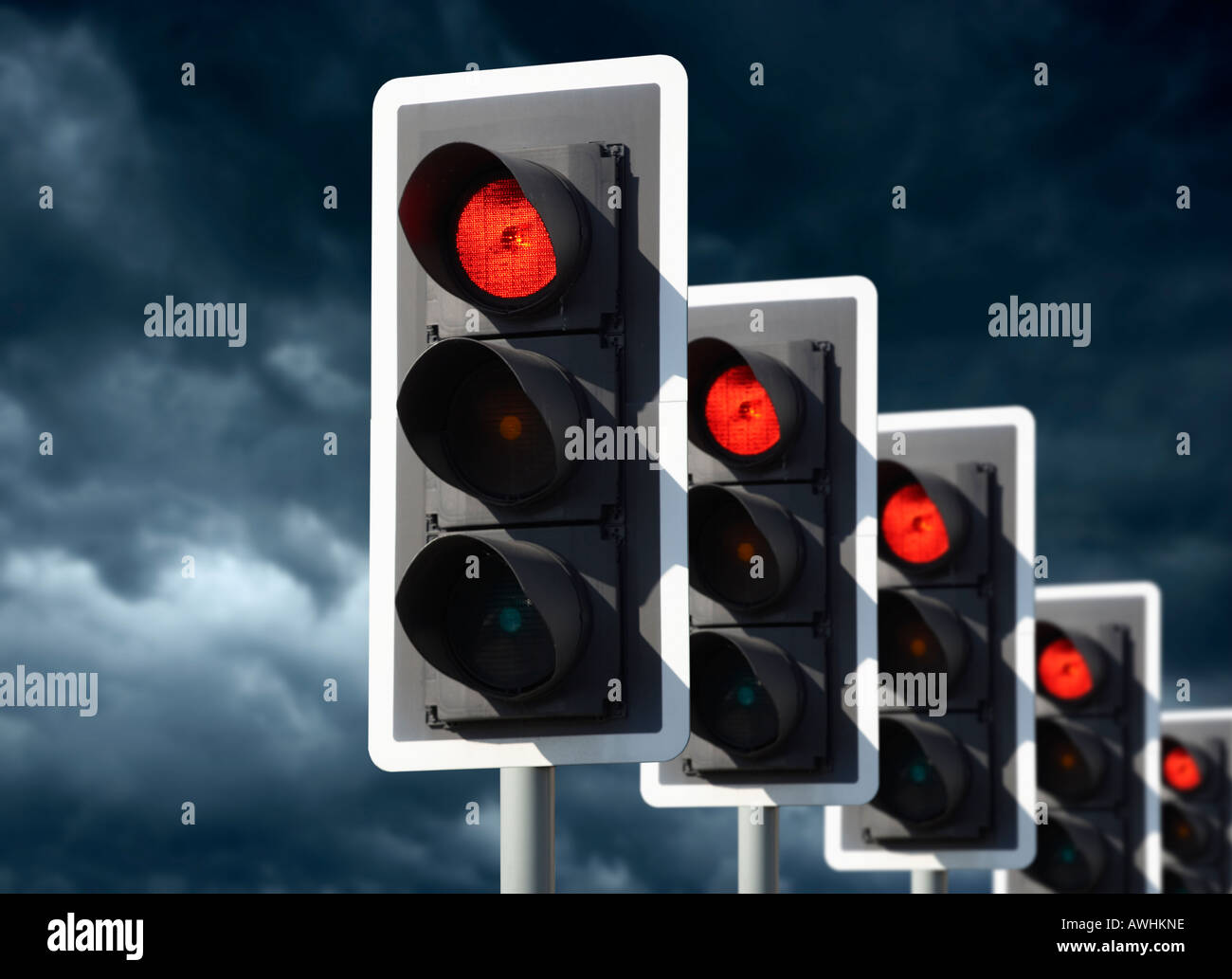 ROW OF FIVE ROAD TRAFFIC LIGHTS SHOWING RED WITH STORMY SKY - Stock Image