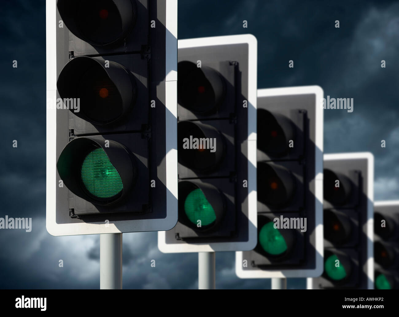 ROW OF FIVE ROAD TRAFFIC LIGHTS SHOWING GREEN WITH STORMY SKY - Stock Image