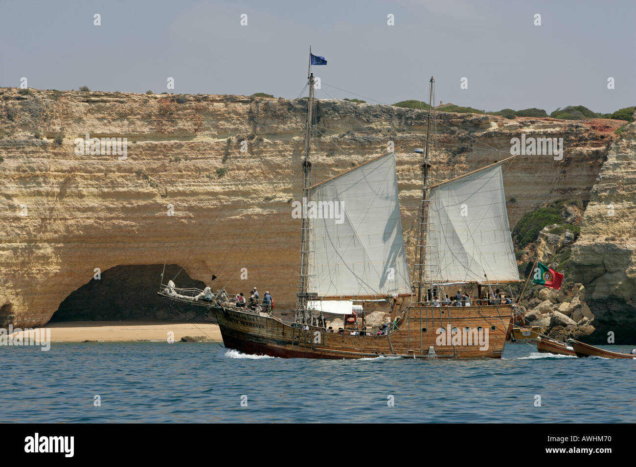A Portuguese reproduction of a caravel l sails past beaches caves and cliffs along the Algarve coast of Portugal. - Stock Image