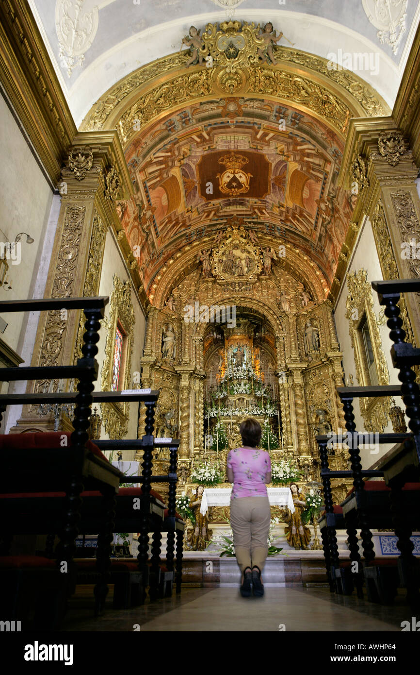 A woman kneels and prays before the gilded alter inside the church of Our Lady of Carmel in Faro Portugal - Stock Image