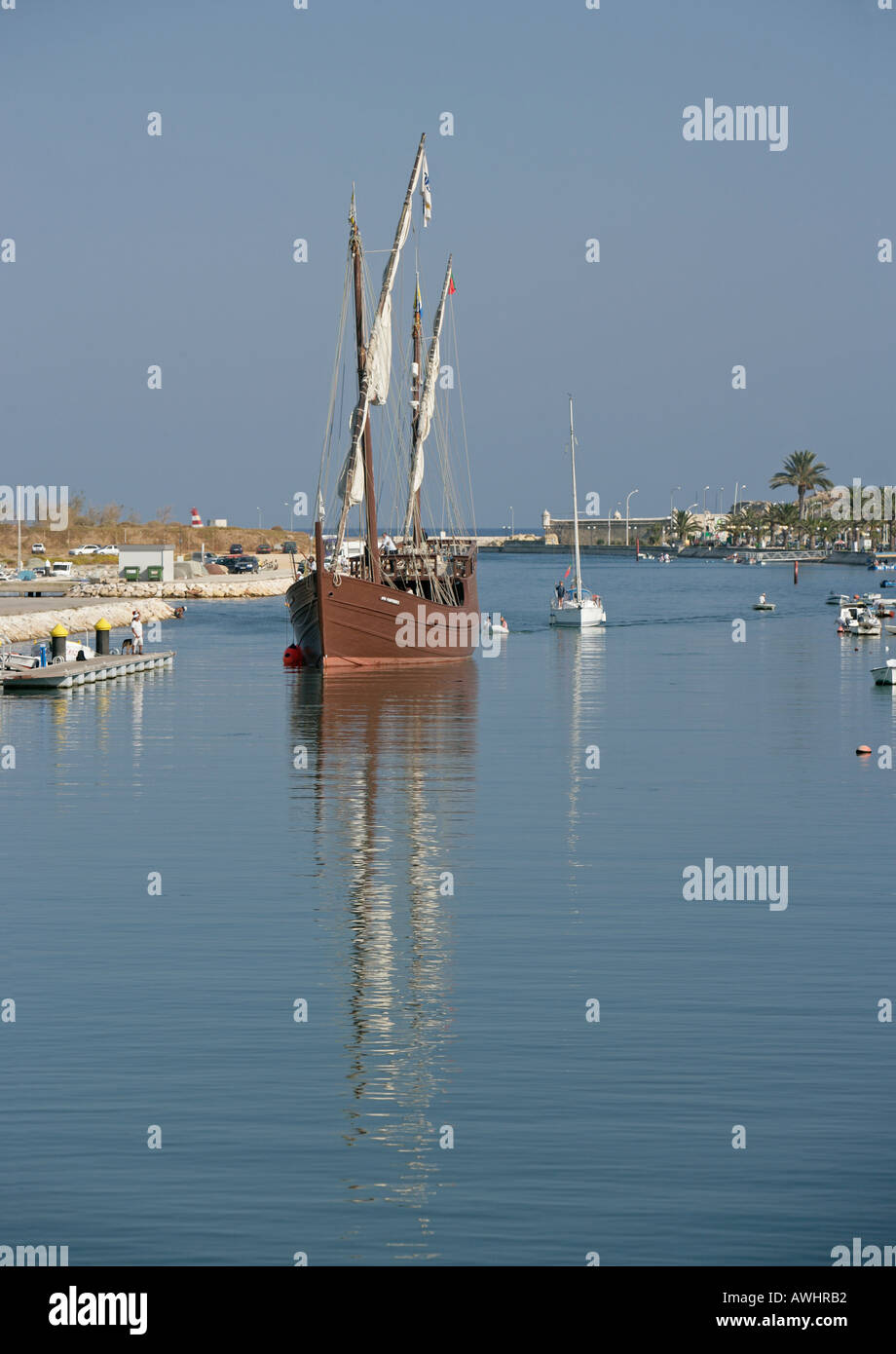 A reproduction of an old caravel comes into the canal leading in from the ocean into the town of Logos Portugal. - Stock Image