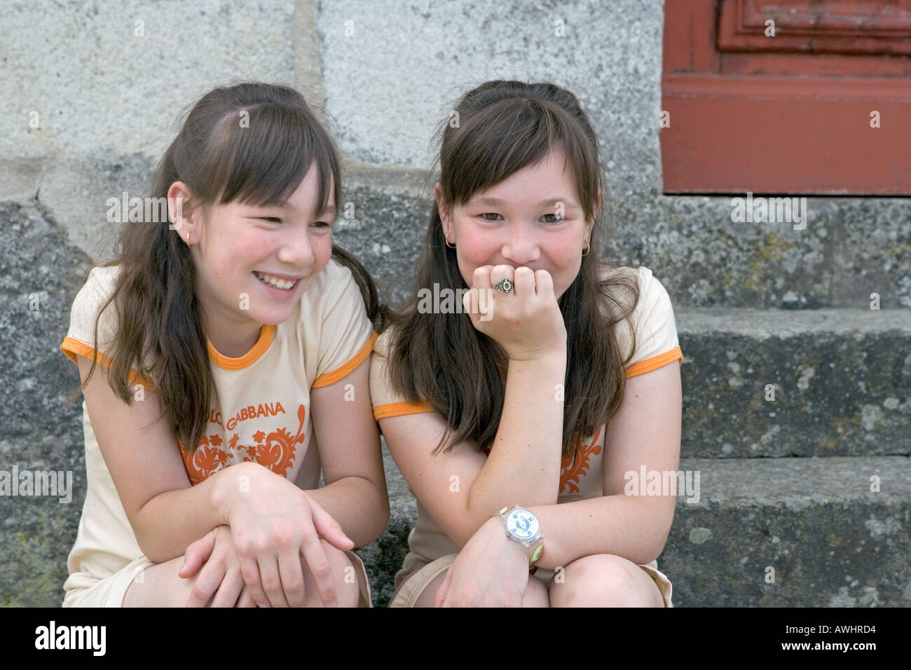 A pair of twin sisters in school uniforms sit on stone steps near their school - Stock Image